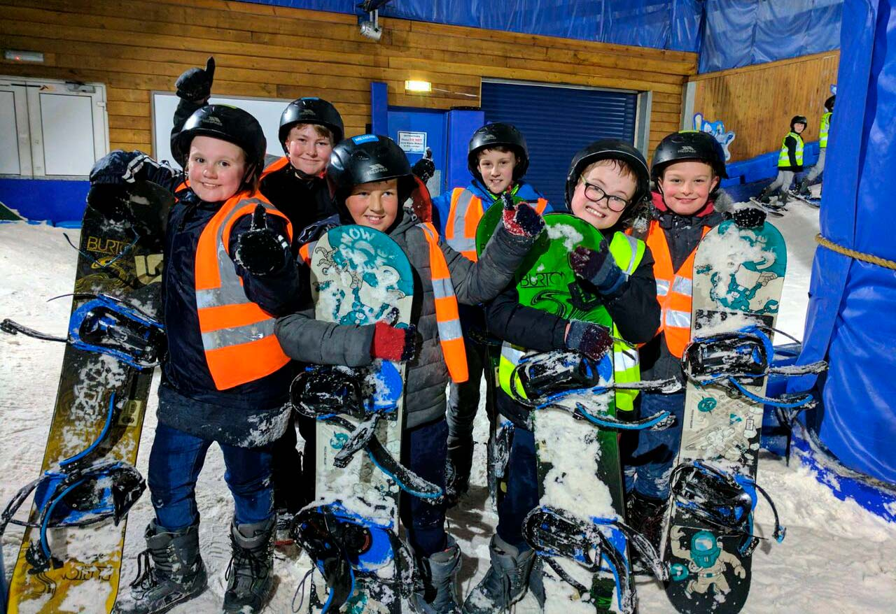 Children having fun learning to snowboard